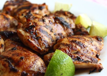 Marinated & fried chicken thighs with lime quarters served on a plate