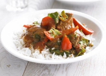 a plate with curried lamb with vegetables on rice