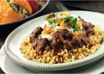 braised lamb with sprinkles of apricots and yoghurt on a plate of couscous